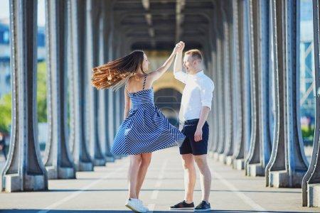 Couple walking along Bir-Hakeim bridge in Paris, France