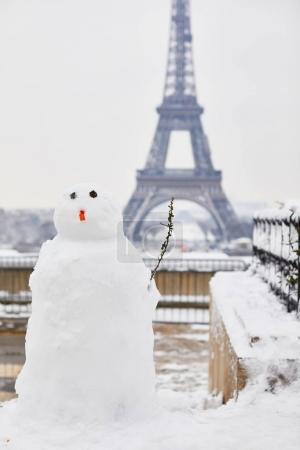 Photo pour Bonhomme de neige drôle et la tour Eiffel sur une journée avec de la neige épaisse. Conditions météo inhabituelles à Paris - image libre de droit