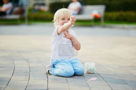 Photo for Adorable little boy drawing with colorful chalks on asphalt. Summer activity and creative games for small kids - Royalty Free Image