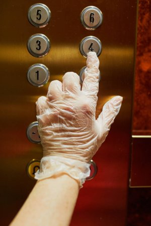 Photo for Woman hand in protective single use glove presses elevator button in a residential apartment building. Quarantine and self-isolation during pandemic and epidemic - Royalty Free Image