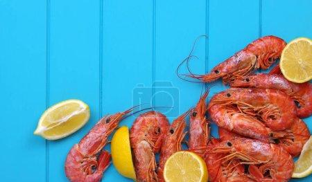 Photo pour Crevettes cuites au citron et aux épices. Fruits de mer servis sur une table en bois. Vue de dessus. Gros plan - image libre de droit