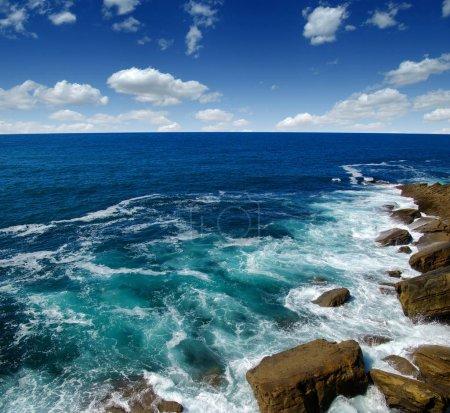 Photo pour Vagues de l'océan s'écrasant sur la côte rocheuse avec embruns - image libre de droit