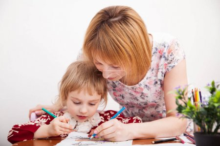 Young mom and her little daughter drawing