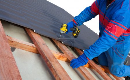 Man worker uses a power drill