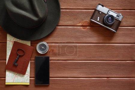 Travel accessories on dark wooden background.