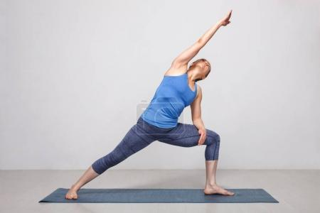 Photo for Woman doing Ashtanga Vinyasa yoga asana Utthita parsvakonasana - extended side angle pose beginner variation on yoga mat on yoga mat in studio on grey bagckground - Royalty Free Image