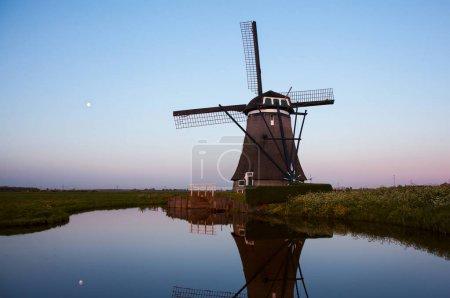 Photo pour Lever de soleil avec des moulins à vent hollandais traditionnels reflétés dans l'eau calme du canal. Paysage avec vieux moulins à vent et canaux, province de Zuid-Holland, Pays-Bas - image libre de droit