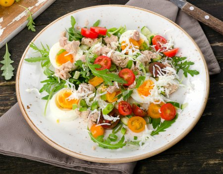 Fresh salad with fish, eggs and tomatoes on  rustic wooden backg