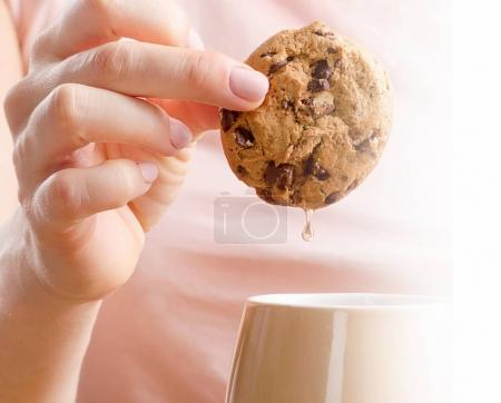 Female hands holding tea cup and cookie.