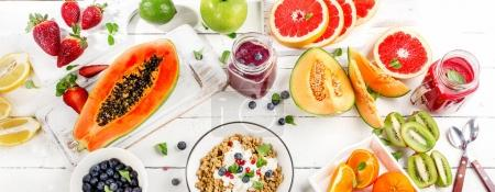 Photo for Breakfast with fresh smoothies, fruit, muesli and berries on wooden background. Banner. Top view - Royalty Free Image