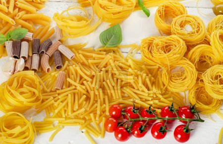 Photo for Variety of types dried pasta and cherry tomatoes. Top view - Royalty Free Image