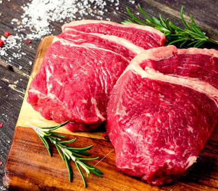 Photo for Raw beef steaks with rosemary on cutting board - Royalty Free Image