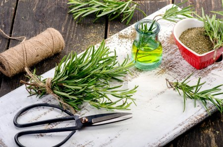 Photo for Fresh and dried Rosemary and oil on wooden table - Royalty Free Image