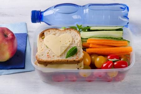 lunch box with sandwich and vegetables