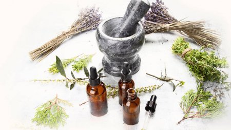 Bottles with organic essential aroma oil for aromatherapy and mortar with herbs