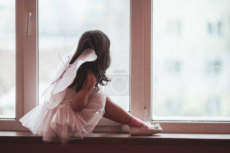 Photo pour Petite fille rêveuse dans un tutu rose dansant regarde par la fenêtre - image libre de droit