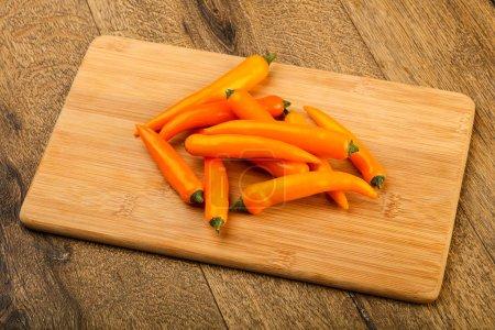 Hot yellow pepper heap over wooden background