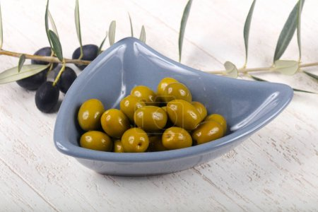 Green olives in the bowl served branch
