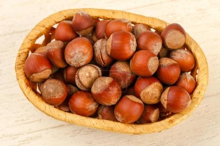 Hazelnuts heap in bowl over wooden background