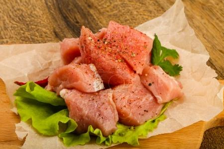 Raw pork pieces with pepper and salt - ready for cooking