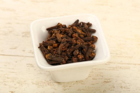 Clove seeds in the bowl - spice for cuisine over wooden background