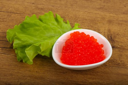 Red caviar in the bowl over wooden background