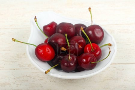 Sweet cherries in the bowl over wooden background