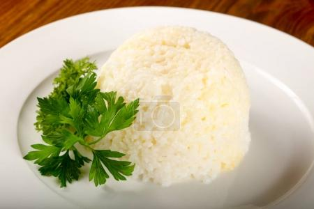Steamed rice with parsley over wooden background