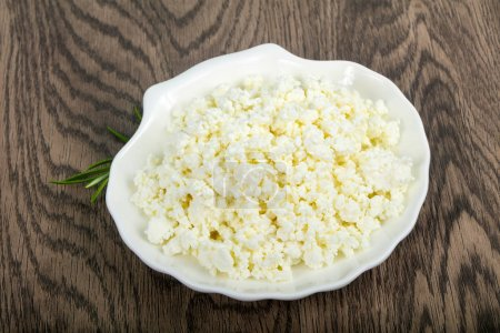 Cottage cheese in the bowl over wooden background