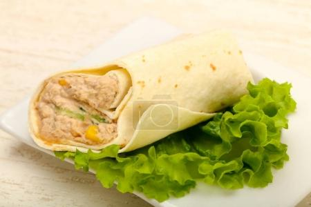 Tuna bread roll with salad leaves over wooden background