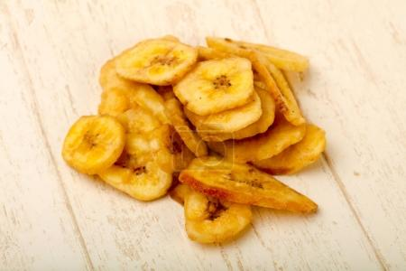 Dry banana chips over wooden background