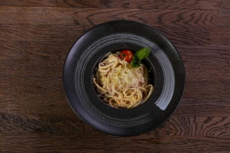 Italian pasta Carbonara served tomato and basil