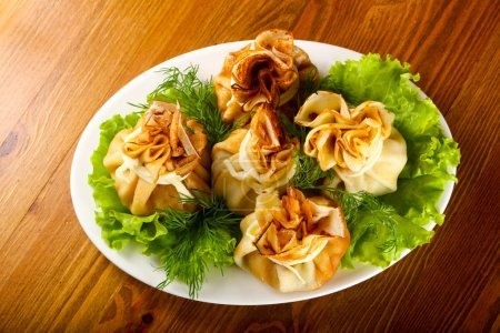 Stuffed pancake with meat over wooden background