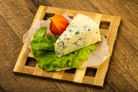 Blue cheese with salad leaves over the wooden background