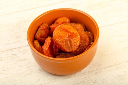 Dried apricots heap in the bowl over wooden background