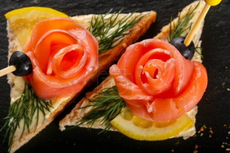 Sandwich with salmon over black background