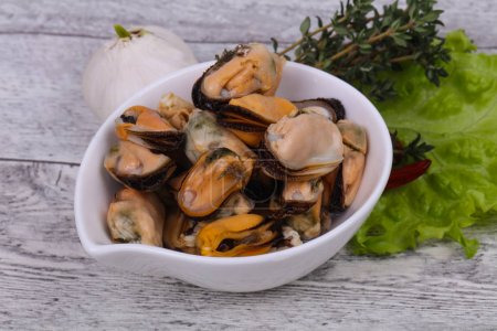 Photo for Pickled mussels in the bowl served pepper, garlic and salad leaves - Royalty Free Image