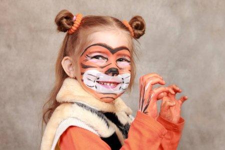 Photo pour Jeune fille souriante avec les mains et un visage peint «tigre» - image libre de droit