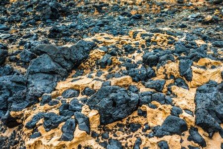 Black stones from hardened volcanic lava in Lanzar...