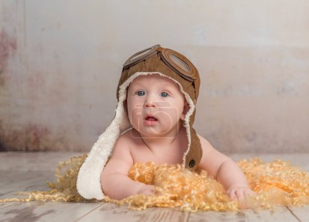 Photo for Lovely little baby in pilot hat crawling on wooden floor - Royalty Free Image