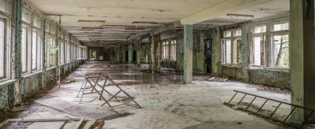 ruined school hall with debris and remains in Pripyat
