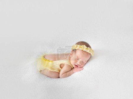 Photo pour Incroyable petit enfant dans un costume tricoté jaune sieste sur son ventre, gros plan - image libre de droit