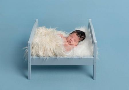 Photo for Lovely hairy newborn sleeping on a tiny bed, covered with a sofr furry blanket - Royalty Free Image
