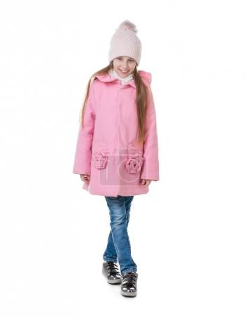 Adorable girl in a pink hat and a coat standing, i...