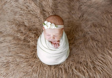baby girl wrapped in blanket with hairband