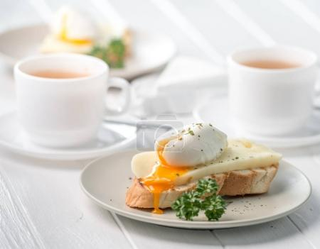 Photo for Delicious sandwich with poached egg and fresh cheese, hot tea in white cup - Royalty Free Image