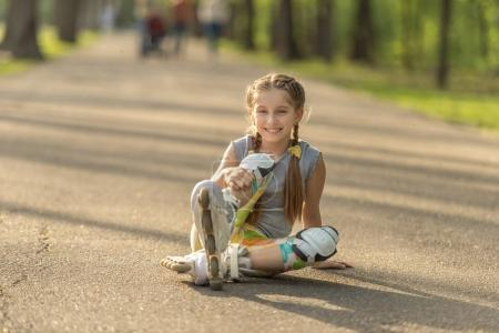 teen girl skating, sitting on asphalt and resting