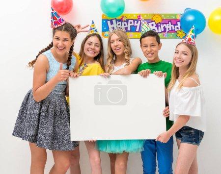 Photo pour Groupe d'adolescents à une fête d'anniversaire tenant bannière blanche - image libre de droit