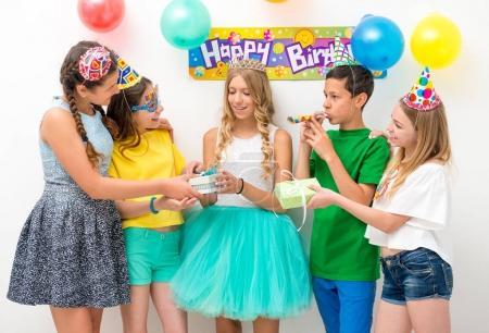 Photo pour Groupe d'adolescents à une fête d'anniversaire donner des cadeaux - image libre de droit