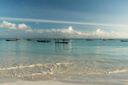 boats with fishermen in ocean near fishing village